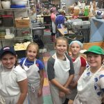 Junior Girl Scouts working at a local bakery.
