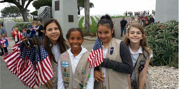 Girl Scouts laying flags at military cemetery