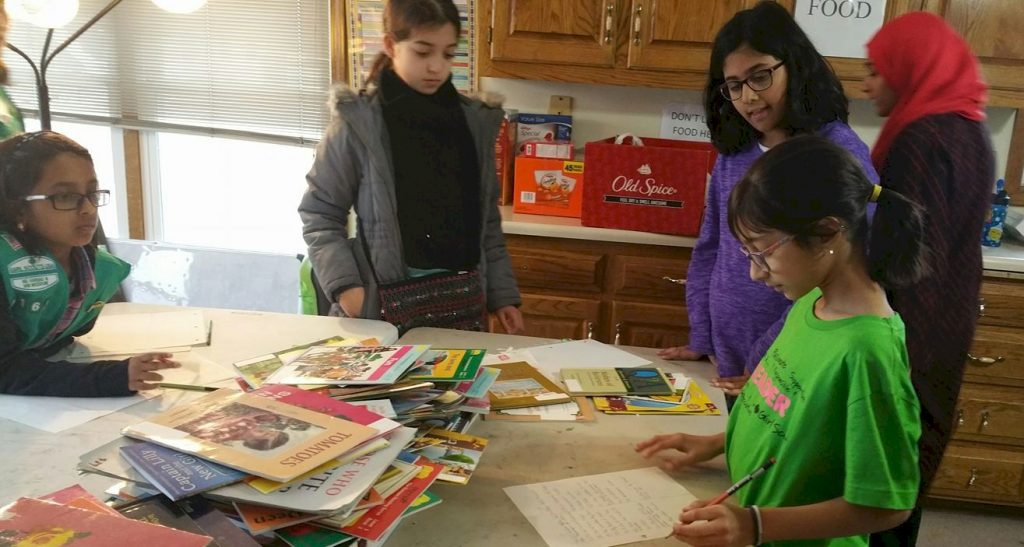 Sister Girl Scout Troops restocking a library.