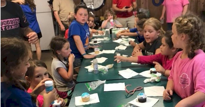 Girl Scout decorating cupcakes.