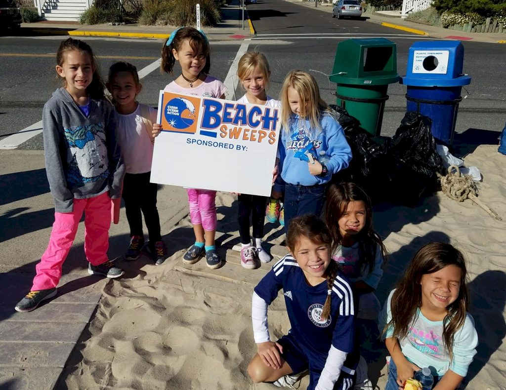 Girls Scouts cleaning up a beach.
