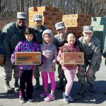 Brownie Girl Scouts donating cookies to the military