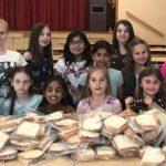Girl Scout Brownies make sandwiches for the local soup kitchen.