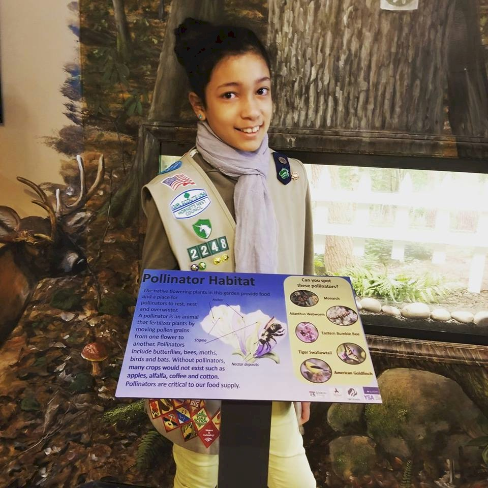 Cadette Girl Scout with donated sign for butterfly garden.
