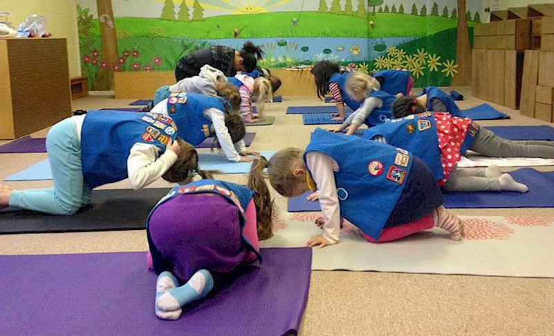 Daisy Girl Scouts doing yoga.