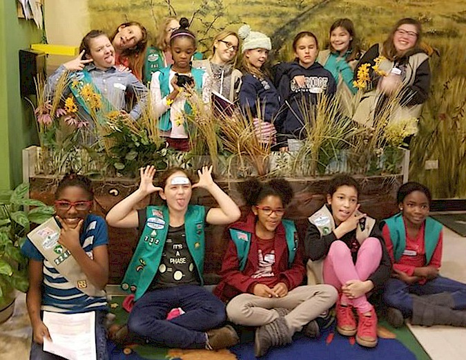 Girl Scouts enhancing a butterfly garden.
